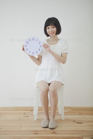椅子に座って時計を持つ女性の写真素材 [FYI00467516]