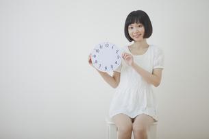 椅子に座って時計を持つ女性の写真素材 [FYI00467524]