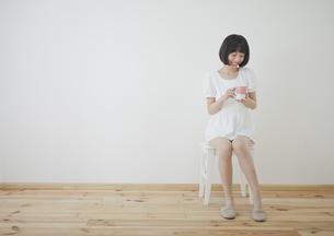 椅子に座ってコップを持つ女性の写真素材 [FYI00467527]