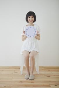 椅子に座って時計を持つ女性の写真素材 [FYI00467531]