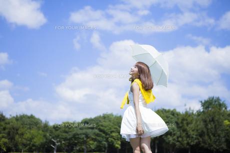 青空の下公園で日傘をさす女性の写真素材 [FYI00467573]