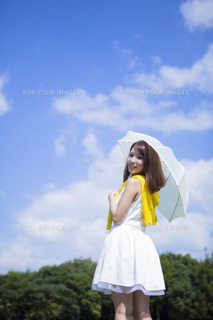 青空の下公園で日傘をさす女性の写真素材 [FYI00467585]