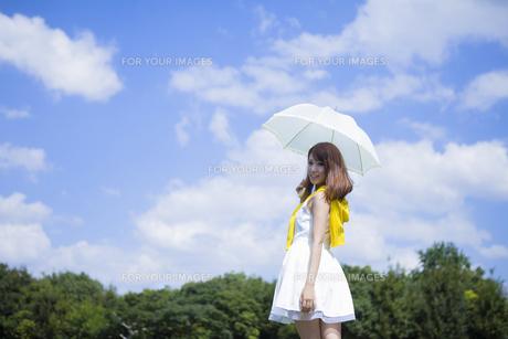 青空の下公園で日傘をさす女性の写真素材 [FYI00467593]