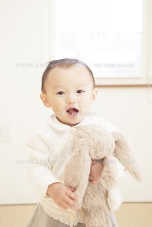ぬいぐるみを持って笑う赤ちゃんの写真素材 [FYI00468060]