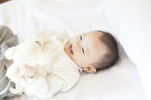 笑顔でぬいぐるみと遊ぶ赤ちゃんの写真素材 [FYI00468150]
