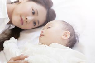 眠る赤ちゃんを見つめる母親の写真素材 [FYI00468188]