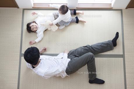 父親と寝転ぶ姉妹の写真素材 [FYI00468206]