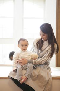 赤ちゃんをひざに上で抱く母親の写真素材 [FYI00468235]