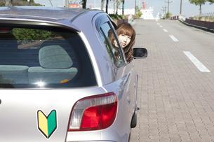 運転席から振り返る、初心者の女性の写真素材 [FYI00468249]