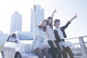 友達と車の前で楽しそうに手を上げる女性の写真素材 [FYI00468260]