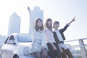友達と車の前で楽しそうに手を上げる女性の写真素材 [FYI00468264]