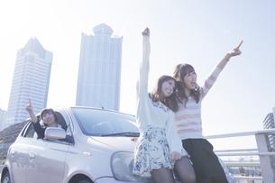 遠くを指差す女性と、車の前で楽しそうに手を上げる友達の写真素材 [FYI00468272]