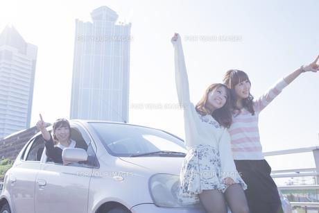 遠くを指差す女性と、車の前で楽しそうに手を上げる友達の写真素材 [FYI00468276]