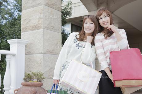 友達とショッピングバッグを持って同じ方向を見つめる女性の写真素材 [FYI00468277]