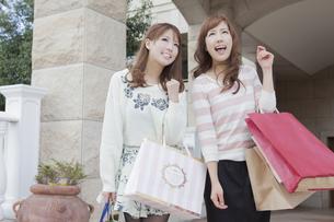 友達とショッピングバッグを持って同じ方向を見つめる女性の写真素材 [FYI00468282]
