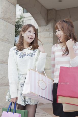友達とショッピングバッグを持って会話をする女性の写真素材 [FYI00468285]