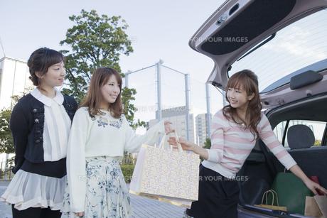 車のトランクから友達にショッピングバッグを渡す女性の写真素材 [FYI00468286]