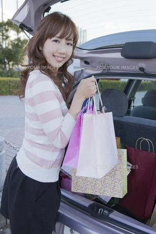 車のトランクにショッピングバッグを積む笑顔の女性の写真素材 [FYI00468288]