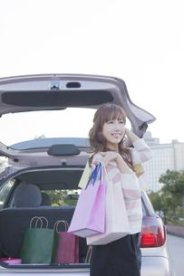 車のトランクを開けて、ショッピングバッグを持つ女性の写真素材 [FYI00468289]