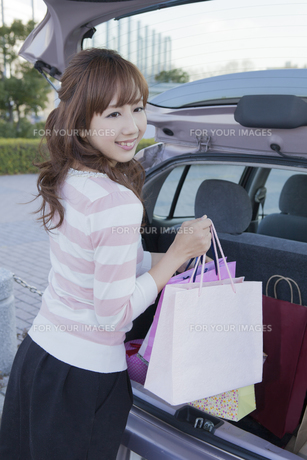 車のトランクにショッピングバッグを積む笑顔の女性の写真素材 [FYI00468293]