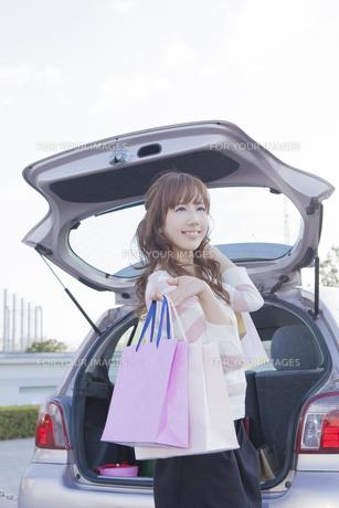 車のトランクを開けて、ショッピングバッグを持つ女性の写真素材 [FYI00468298]