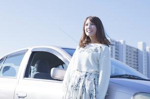 車にもたれて立つ女性の写真素材 [FYI00468311]
