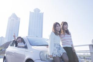 遠くを指差す女性と、車の前で楽しそうに話す友達の写真素材 [FYI00468314]