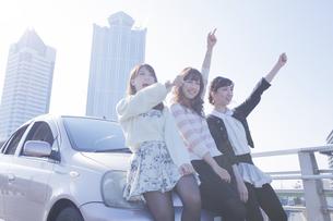 友達と車の前で楽しそうに指差す女性の写真素材 [FYI00468315]
