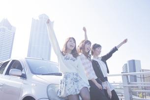 友達と車の前で楽しそうに手を上げる女性の写真素材 [FYI00468317]