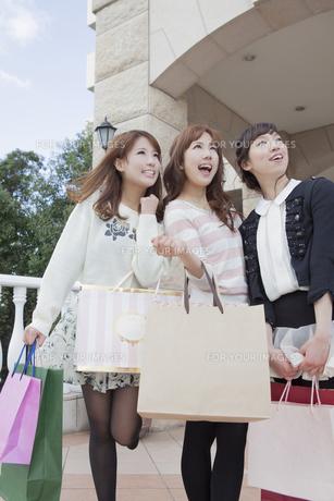 友達とショッピングバッグを持って同じ方向を見つめる笑顔の女性の写真素材 [FYI00468326]