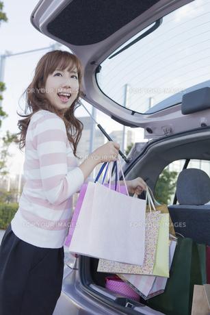 車のトランクにショッピングバッグを積む女性の写真素材 [FYI00468327]