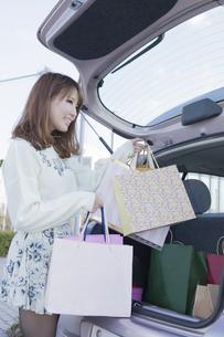 車のトランクにショッピングバッグを積む笑顔の女性の写真素材 [FYI00468340]