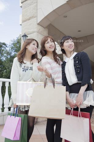 友達とショッピングバッグを持って同じ方向を見つめる女性の写真素材 [FYI00468345]
