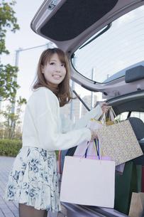 車のトランクにショッピングバッグを積む女性の写真素材 [FYI00468347]