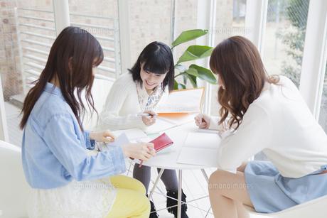 椅子に座ってノート見せ合う女子学生の写真素材 [FYI00468351]