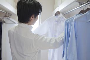クローゼットでシャツを選ぶ男性の写真素材 [FYI00468518]