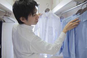 クローゼットでシャツを選ぶ男性の写真素材 [FYI00468529]