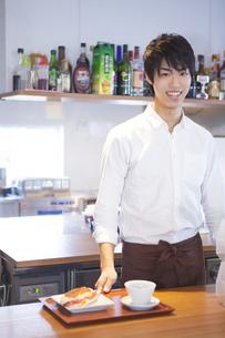 カウンターの男性カフェ店員の写真素材 [FYI00468586]