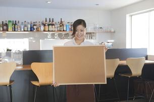 コルクボードを持つ女性カフェ店員の写真素材 [FYI00468617]