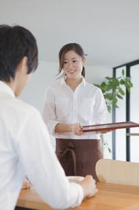 笑顔で接客する女性カフェ店員の写真素材 [FYI00468636]