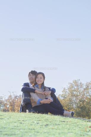 芝生の上で仲良く座るカップルの写真素材 [FYI00468650]