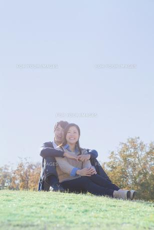 芝生の上で仲良く座るカップルの写真素材 [FYI00468651]
