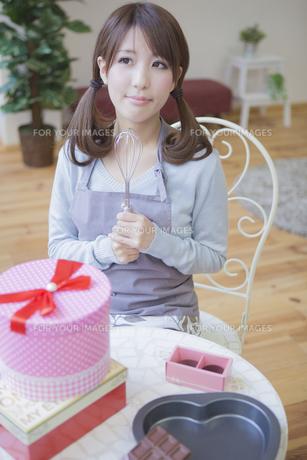 机の上にプレゼントとチョコレートを置いて泡立て器を持つ女性の写真素材 [FYI00468723]