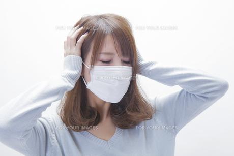 頭をおさえるマスクをした女性の写真素材 [FYI00468724]