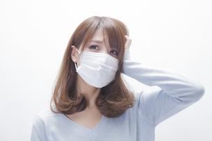 頭をおさえるマスクをした女性の写真素材 [FYI00468729]