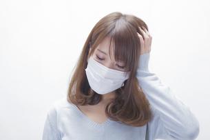 頭をおさえるマスクをした女性の写真素材 [FYI00468737]