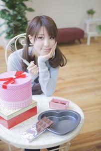 机の上にプレゼントとチョコレートを置いて泡立て器を持つ女性の写真素材 [FYI00468740]