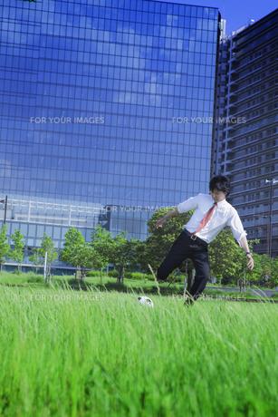 サッカーボールを蹴るビジネスマンの写真素材 [FYI00468767]