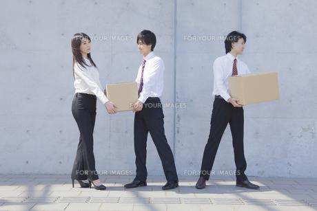 段ボールを運ぶビジネスマンとビジネスウーマンの写真素材 [FYI00468816]