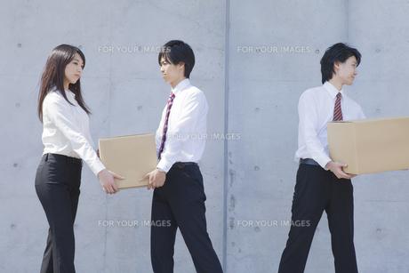 段ボールを運ぶビジネスマンとビジネスウーマンの写真素材 [FYI00468831]